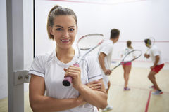 Playing squash with friends. Squash player and people in the background Stock Images