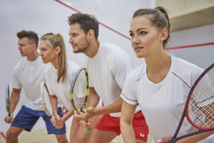 Playing squash with friends. They seem to be ready to start the game Stock Photos