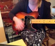 Playing or strumming a guitar. Blurred hand movement. A person playing or strumming a guitar. The hand is blurred as it moved across the strings Stock Photo