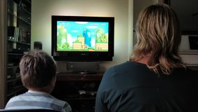 Playing Super Mario Bros on wii with mama royalty free stock images