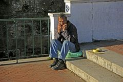 Playing for survival. Lisbon, Portugal - November 26, 2013: a man sitting on steps and playing music for passerby Royalty Free Stock Image