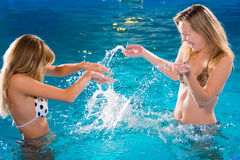 Playing in swimming pool Stock Images