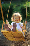 Playing on the swings. Cute little girl playing on the swings stock image