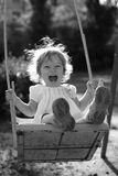 Playing on the swings after summer rain. Playing on the swings - black and white photo with orange filter effect, shallow depth of field, back lighting royalty free stock photo