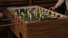 Playing table football. Two men playing table football yellow and white players foosball stock video footage