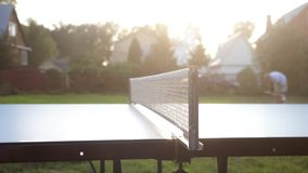 Playing table tennis game in slow motion outdoor close-up on sunny day. 3840x2160. Playing table tennis game outdoor close-up stock video