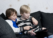 Playing with a tablet. Two young kids in a sofa having fun together with a tablet Stock Image