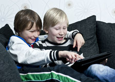 Playing with a tablet. Two young kids in a sofa having fun together with a tablet Royalty Free Stock Images