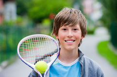 Playing tennis. Teenager holding a tennis racket with ball and smiling at the camera Stock Images