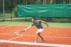 Playing tennis. Confident young man in sports clothes playing tennis on tennis court stock image