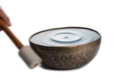 Playing Tibetian singing bowl on white Stock Images