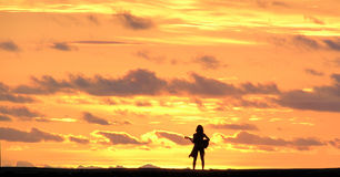 Playing to the Sun. Woman standing on pier playing guitar to the beautiful sunset royalty free stock photo