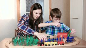 Playing together. Mom and son are playing a wooden railway with train, wagons and tunnel with plastic soldiers sitting. At the table stock video