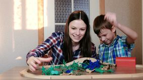 Playing together. Mom and son are playing a wooden railway with train, wagons and tunnel with plastic soldiers sitting. At the table stock footage