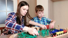 Playing together. Mom and son are playing a wooden railway with train, wagons and tunnel with plastic soldiers sitting. At the table stock video footage
