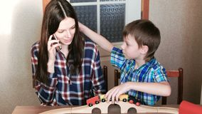 Playing together. Mom talk her phone and son is playing a wooden railway with train, wagons and tunnel sitting at the