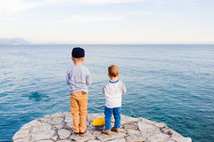Playing always together. Rear view shot of two little boys standing on a pier at the ocean Royalty Free Stock Images