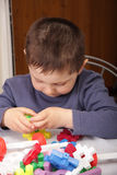 Playing with toy blocks. Boy in grey jacket playing with toy blocks Royalty Free Stock Photos