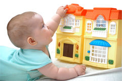 Playing with a toy house. A child playing with toy house Royalty Free Stock Photos