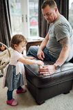 Playing with Toys at Home. Little girl and her father are playing with toys together at home stock photo