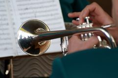 Playing trumpet. Musician is plaing on trumpet. Reflection on trumpet's surface. Printed music on a background Stock Photography