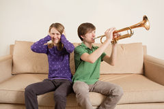 Playing trumpet badly. Photo of a brother playing his trumpet too loudly, or badly, and annoying his sister Stock Image