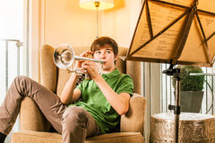 Playing the trumpet at home. Photo of a teenage male practicing his trumpet at home Stock Photography