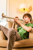Playing the trumpet in the living room. Photo of a teenage male practicing his trumpet at home Royalty Free Stock Photography