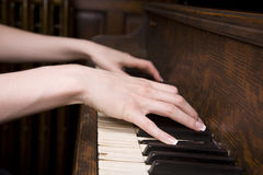 Playing a tune. Woman's hands on an old piano playing a song. Focus is on the closer hand Stock Image