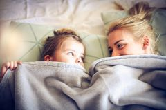 Playing under blanket with mommy. Little girl. royalty free stock images