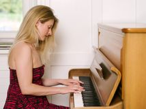 Playing an upright piano. Photo of a happy blond female in her early thirties playing the piano at home Stock Photography