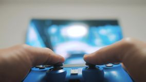 Playing video console on tv. Hand hold new joystick playing video console on tv . Gamer play lifestyle game with gamepad. Controller. Gaming man holding stock footage
