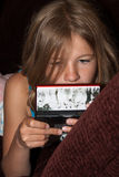 Playing video game. Young ten year old blond girl staring intensely at a hand held video game stock images