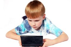 Playing A Video Game. A six year old boy wearing blue who is playing a hand held video game Stock Images