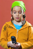 Playing a video game. Young girl with green kerchief looking a typing on a mobile phone Stock Photo