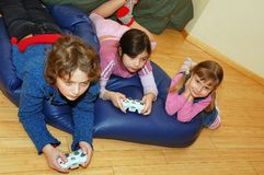 Playing Video Game. Three kids  playing a video game on the floor Stock Photo