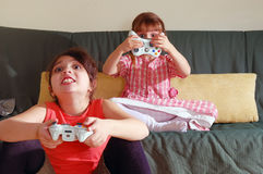 Playing Video Game. Two exited little girls playing a video game Royalty Free Stock Photo