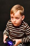Playing video game. Cute blond   happy Child playing  Playing video game Stock Images