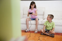 Playing video games. Children playing video games in the living room Royalty Free Stock Image