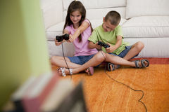 Playing video games. Children playing video games in the living room Royalty Free Stock Images