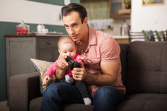 Playing video games and babysitting. Young attractive dad playing video games at home while taking care of her baby girl Royalty Free Stock Images