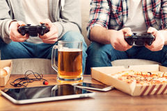 Playing video games. Close-up of two men playing video games while sitting on sofa Royalty Free Stock Images