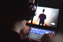 Playing video games with laptop. Young man plays action game. Stock Image