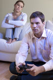 Playing Videogame. Man playing videogames, woman disappointed and bored Stock Photography