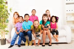 Playing videogame with friends. Group of diversity looking kids, boys and girls playing videogame sitting on the sofa holding game controllers Royalty Free Stock Images
