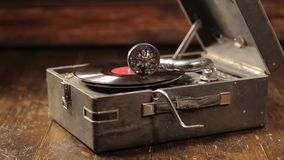 Playing vinyl records on a retro gramophone, potefone. Close-up. Men`s hands put a vinyl record and start a gramophone. HD stock video
