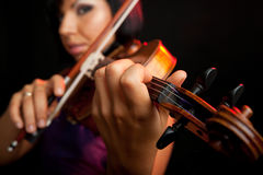 Playing the violin. Young beautiful female violinist, focus on her fingers stock image