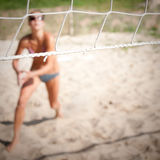 Playing volley ball. Aggressive woman playing netted ball on beach Stock Image