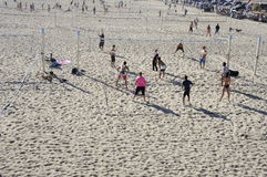Playing Volley Ball. These group of men and women are having a game of playing volley Ball at the white sand of Huntington Beach Royalty Free Stock Photos