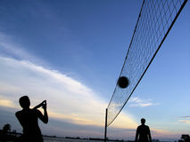 Playing volleyball at dusk. Area is in Sentosa Island, Singapore. The sunset was colourful and these men were having a game of volleyball. Picture was taken to Stock Photos